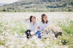 Dos mujeres bonitas jovenes que tienen comida campestre con té en campo de la manzanilla Foto de archivo libre de regalías