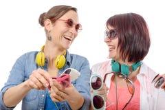 Dos mujeres bonitas que intentan en las gafas de sol Imágenes de archivo libres de regalías