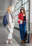 Dos mujeres bonitas que se colocan en el terminal con una maleta, una mochila y un pasaporte Fotos de archivo libres de regalías