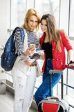 Dos mujeres bonitas que se colocan en el terminal con una maleta, una mochila y un pasaporte, mirada en el teléfono Fotos de archivo libres de regalías