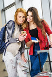 Dos mujeres bonitas que se colocan en el terminal con una maleta, una mochila y un pasaporte, mirada en el teléfono Imagenes de archivo