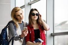 Dos mujeres bonitas que se colocan en el terminal con una maleta, una mochila y un pasaporte, mirada en el teléfono Imagen de archivo libre de regalías