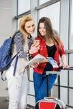 Dos mujeres bonitas que se colocan en el terminal con una maleta, una mochila y un pasaporte, mirada en el teléfono Foto de archivo