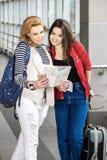Dos mujeres bonitas que se colocan en el terminal con una maleta, una mochila y una mirada en el mapa Foto de archivo