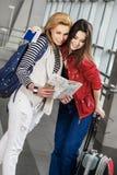 Dos mujeres bonitas que se colocan en el terminal con una maleta, una mochila y una mirada en el mapa Imagen de archivo