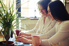 Dos mujeres bonitas que trabajan en el ordenador portátil junto Imagenes de archivo