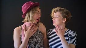 Dos mujeres bonitas rubias jovenes que se colocan cercanas y que hablan, felices y alegres, aislado en fondo negro almacen de metraje de vídeo