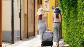 Dos mujeres caminan a lo largo del callejón y a su derecha una pared verde almacen de metraje de vídeo