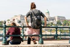 Dos mujeres caucásicas jovenes que se sientan y que se inclinan contra una verja de acero por el río Danubio en Budapest Hungría Fotos de archivo
