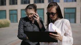 Dos mujeres cerca del centro de negocios llaman en el teléfono con el jefe que le dice la información analítica importante almacen de video