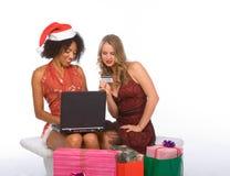 Dos mujeres: Compras en línea de la Navidad usando la computadora portátil imágenes de archivo libres de regalías