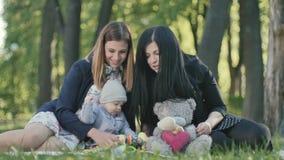 Dos mujeres con el bebé lindo que juega los juguetes en una sobrecama en parque almacen de metraje de vídeo