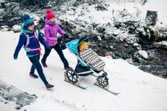 Dos mujeres con el cochecito de bebé que disfruta del invierno en bosque, tiempo de la familia imagen de archivo libre de regalías
