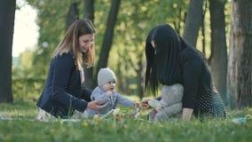 Dos mujeres con el niño pequeño que se relaja en la sobrecama en un parque verde almacen de metraje de vídeo