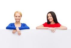 Dos mujeres con el tablero blanco en blanco grande Foto de archivo libre de regalías