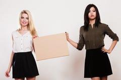 Dos mujeres con el tablero en blanco Imágenes de archivo libres de regalías