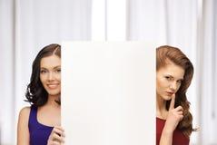 Dos mujeres con el tablero en blanco Imagen de archivo