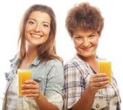 Dos mujeres con el zumo de naranja Foto de archivo libre de regalías