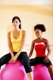 Dos mujeres con la bola de la aptitud en gimnasia Imágenes de archivo libres de regalías