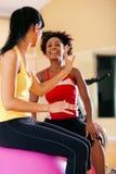 Dos mujeres con la bola de la aptitud en gimnasia Foto de archivo libre de regalías