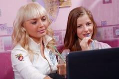 Dos mujeres con la computadora portátil Imagenes de archivo