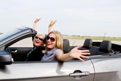 Dos mujeres con los brazos para arriba en convertible Imagenes de archivo