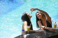 Dos mujeres con los cócteles en piscina Foto de archivo libre de regalías