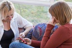 Dos mujeres con los teléfonos elegantes Imagen de archivo libre de regalías