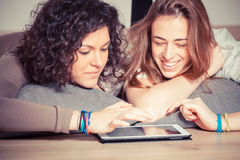 Dos mujeres con PC de la tablilla Fotografía de archivo