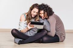 Dos mujeres con PC de la tablilla Foto de archivo libre de regalías