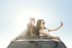 Dos mujeres con smartphone en el tejado del coche Imágenes de archivo libres de regalías
