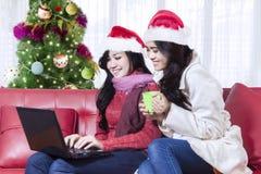 Dos mujeres con un ordenador portátil en el tiempo de la Navidad Imagenes de archivo