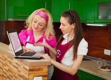 Dos mujeres con un ordenador portátil que busca una receta en Internet Foto de archivo libre de regalías