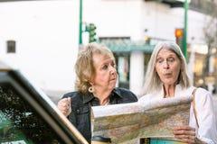 Dos mujeres confusas que comprueban un mapa fotografía de archivo
