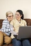 Dos mujeres conversación y trabajo en la computadora portátil Imagen de archivo