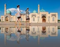 Dos mujeres dan un paseo delante de la mezquita del Khast-imán, reflejada adentro Foto de archivo