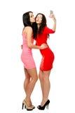Dos mujeres de abarcamiento del soporte de los jóvenes envían beso Foto de archivo libre de regalías