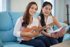 Dos mujeres de Asia se están divirtiendo que juega el ukelele y que sonríe en el hom imagen de archivo libre de regalías