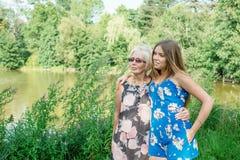 Dos mujeres de diversas generaciones están cerca de una charca en el verano Abrazo de la madre y de la hija Abuela y nieta Fotografía de archivo libre de regalías