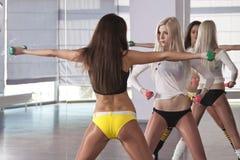 Dos mujeres de la aptitud con pesas de gimnasia Foto de archivo libre de regalías