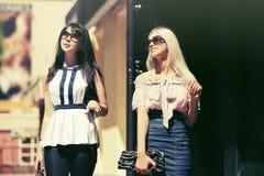 Dos mujeres de la moda de los jóvenes que caminan en la calle de la ciudad fotos de archivo