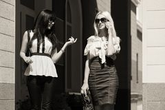 Dos mujeres de la moda de los jóvenes que caminan en calle de la ciudad fotos de archivo libres de regalías
