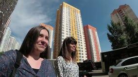 Dos mujeres de los amigos que caminan en la calle en ciudad, amistad y unidad metrajes