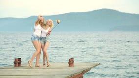 Dos mujeres de los amigos que toman el selfie con el teléfono móvil cerca del río Dos chicas jóvenes que gozan cerca del río y qu metrajes