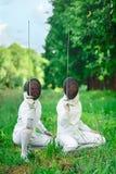 Dos mujeres de los cercadores que se ponen en cuclillas abajo con los estoques que destacan Fotos de archivo