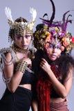 Dos mujeres de los modelos en el vestido del traje del guerrero y de flores fotos de archivo libres de regalías