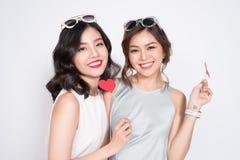 Dos mujeres de moda en los vestidos agradables que se unen y control Imagen de archivo