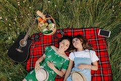 Dos mujeres de moda jovenes alegres que se acuestan en la manta de la comida campestre y que se relajan Fotos de archivo