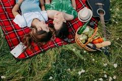 Dos mujeres de moda jovenes alegres que se acuestan en la manta de la comida campestre y que se relajan Imágenes de archivo libres de regalías