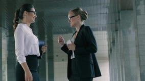 Dos mujeres de negocios amistosas que hablan feliz tomar tiempo del trabajo almacen de metraje de vídeo